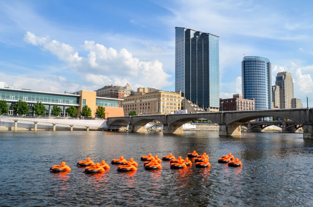 """SOS (Safety Orange Swimmers)"" by A+J Art + Design, in the Grand River near Ah-Nab-Awen Park"